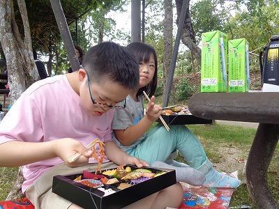 動物園でお弁当を食べる児童たち