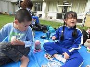 学校の中庭で弁当を食べる子どもたち