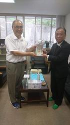 校長に自動消毒器をお渡している松本会長様